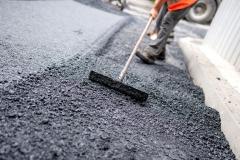 Worker levelling fresh asphalt on a road construction site, indu